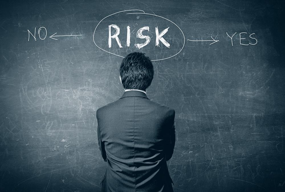 Mann steht vor Tafel mit Risikoentscheidung