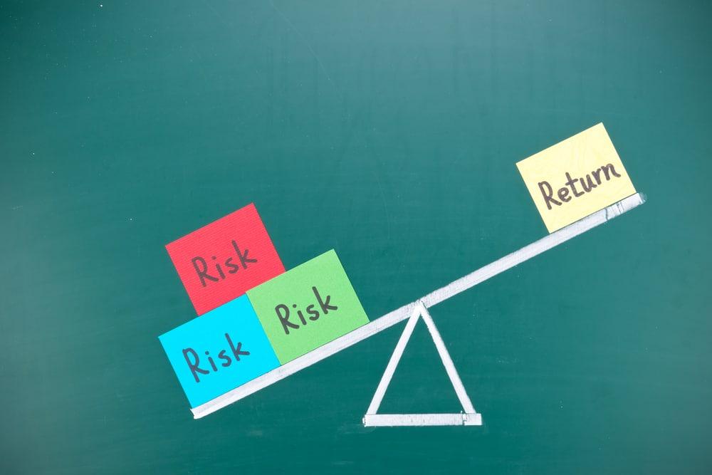 """Grafik mit Waage, die nach """"Risiko"""" ausschlägt."""