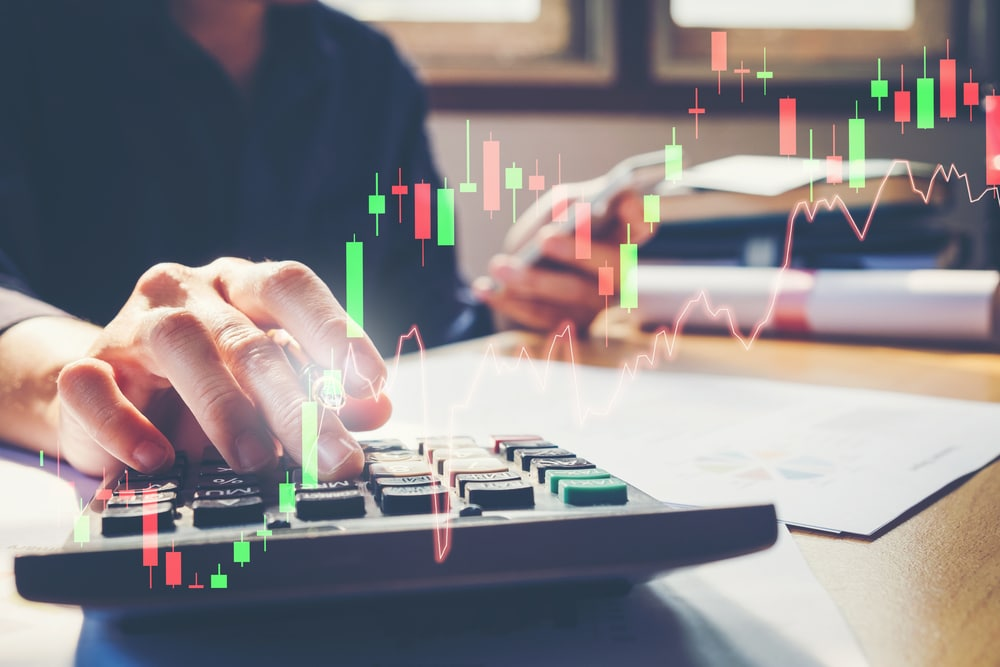 Ein Aktienchart ist zu sehen, dahinter eine Hand, die Zahlen in einen Rechner tippt