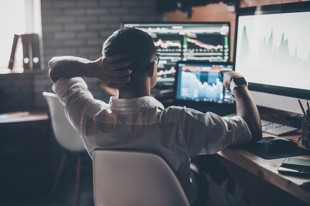 Mann sitzt vor zahlreichen Monitoren mit Kurscharts